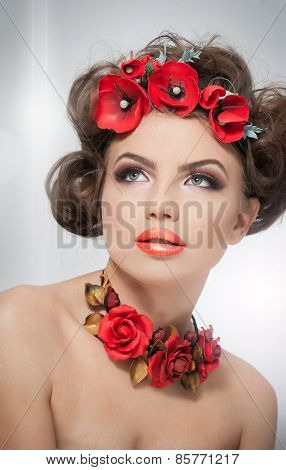 Portrait of beautiful girl in studio with red flowers in her hair and red roses around her neck