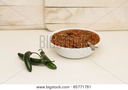 White Bowl Of Chili With Three Peppers