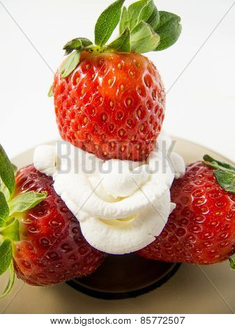 Three strawberries and cream on a plate