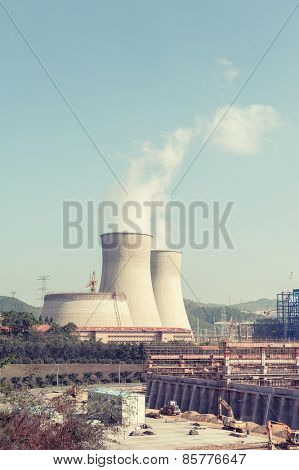 coal power plant against sun with chimneys and huge fumes