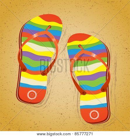Beach slippers on sand.