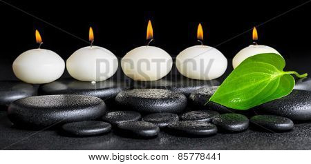 Spa Background Of Row White Candles And Green Leaf On Black Zen Stones Background With Dew, Panorama
