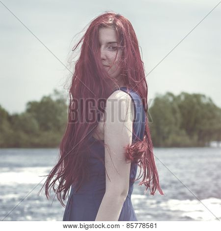 red-haired woman standing in the river
