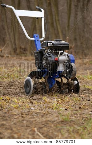 Small garden cultivator on just plowed plot of land