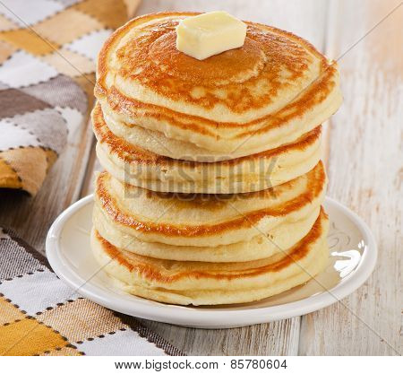 Stack Of Small Pancakes On A White Wooden Table