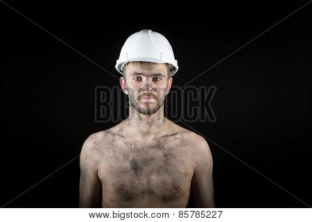 young handsome man in a dirty helmet