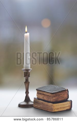 Old Two Prayer  Books And Burning Candle With A Candlestick