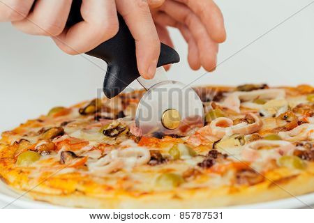 Pizza Being Cut By Cutter