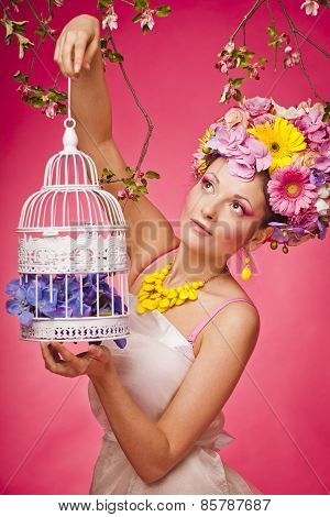 Spring portrait woman with a birdcage and flowers