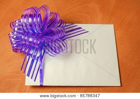 Close Up Of A Note Card With Violet Bow On Wooden Background