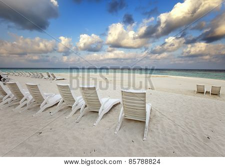 Empty beach chairs on sand by the sea at sunrise