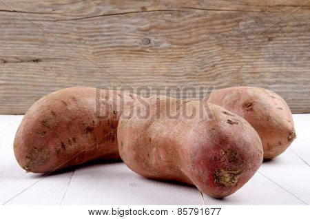 Raw Organic Sweet Potato On White Wood
