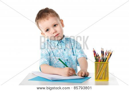 Diligent Little Boy Draws With Crayons