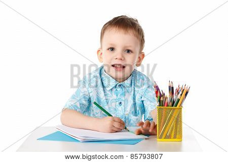 Smiling Little Boy Draws With Crayons
