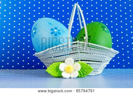 Blue And Green Easter Eggs In A Basket With White Flower