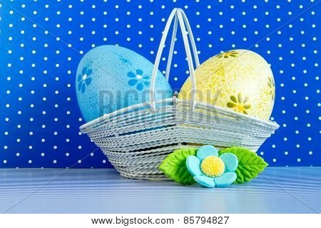 Blue And Yellow Easter Eggs In A Basket With Blue Flower