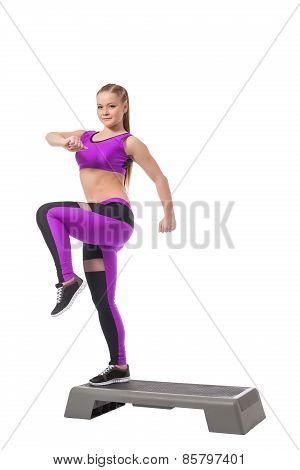 Lovely athletic girl training on stepper