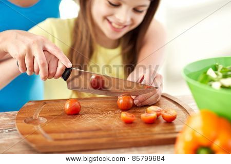 food, family, cooking and people concept - close up of happy girl and mother making dinner and chopping cherry tomatoes on cutting board with knife in kitchen