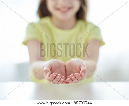 people, charity, childhood and advertisement concept - close up of child cupped hands at home