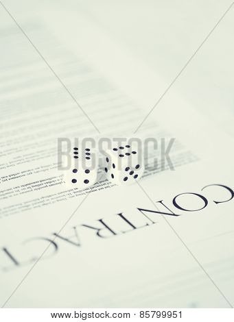 picture of contract paper with gambling dices