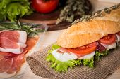 stock photo of baguette  - Ham and cheese salad submarine sandwich from fresh baguette on burlap - JPG
