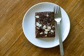 picture of brownie  - Homemade Chocolate Brownie on a dark plate against a dark background - JPG