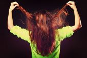 pic of pulling hair  - Young woman teen girl pulling her long brown hair on black - JPG