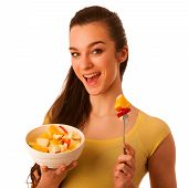 image of beautiful senior woman  - Beautiful happy asian caucasian woman in yellow t shirt eating fruit salad as a healthy lifestyle concept isolated over white - JPG