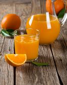 foto of orange-juice  - Glass of freshly pressed orange juice with slice of orange fruit on wooden table. Selective focus is on the glass.
