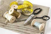 Постер, плакат: Measuring tape threads and scissors
