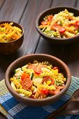 picture of sweet-corn  - Two rustic bowls of pasta salad made of tricolor fusilli sweet corn cucumber cherry tomato and sausage photographed with natural light  - JPG