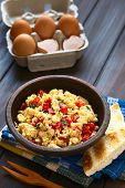 stock photo of scrambled eggs  - Scrambled eggs made with red bell pepper and green onion in rustic bowl with toasted bread on the side and eggs in the back photographed with natural light  - JPG