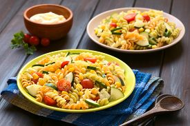 foto of sweet-corn  - Two plates of vegetarian pasta salad made of tricolor fusilli sweet corn cucumber and cherry tomato with mayonnaise in the back photographed with natural light  - JPG