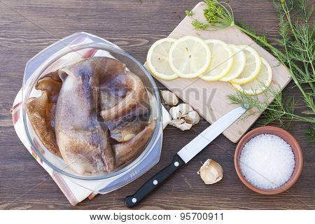 Fresh squid carcass in a glass pot with herbs and sliced lemon