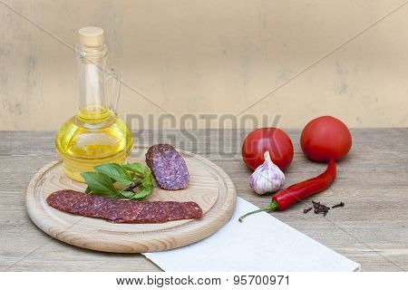 Salami sausage and sunflower oil in the bottles with herbs, tomatoes and spices on wooden table