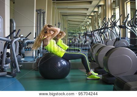 Young Fit Woman Doing Sit-ups On Exercise Ball In Gym