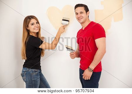 Couple In Love Painting A Wall