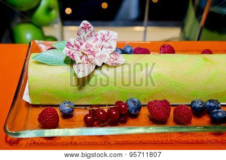 Green Tea Swiss Roll Cake On Glass Dish With Fresh Berries, Rasberries And Cherries