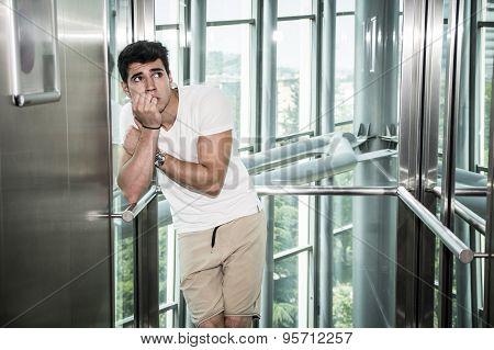 Scared young man desperate in stuck elevator