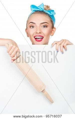 Cheerful young woman is hiding behind white barrier