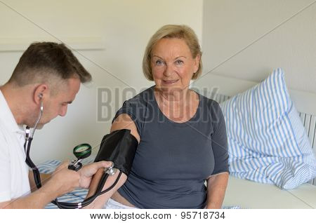 Doctor Taking The Blood Pressure Of An Old Lady