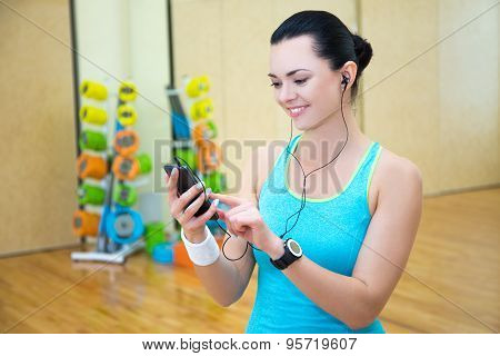 Beautiful Sporty Woman Listening Music In Gym
