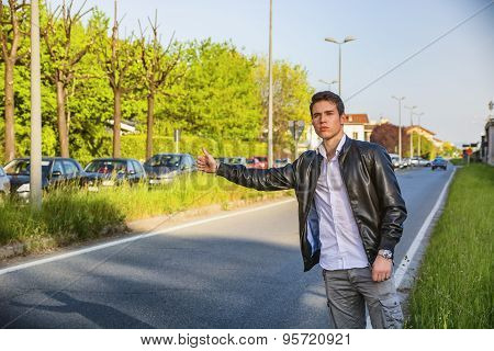 Handsome young man, hitchhiker waiting on roadside