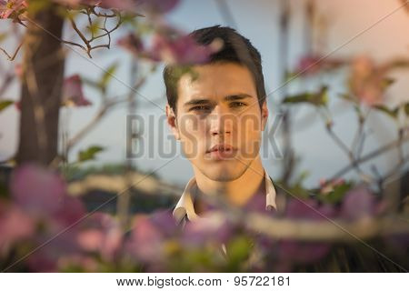 Good looking male model at countryside, among flowers