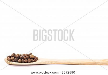 jamaica pepper in wooden spoon isolated.
