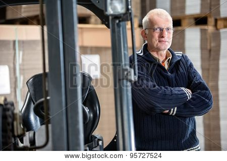 Portrait of confident male worker standing arms crossed while leaning on forklift at warehouse