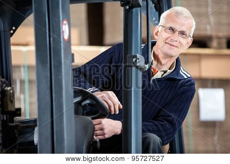 Portrait of confident male worker sitting in forklift at distribution warehouse