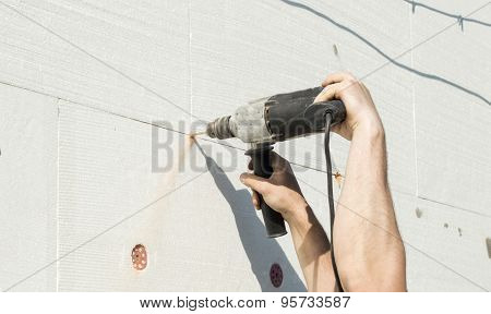 The Process Of Drilling Holes In The White Polyfoam