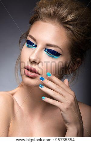 Beautiful girl with bright creative fashion makeup and blue nail polish. Art beauty design.