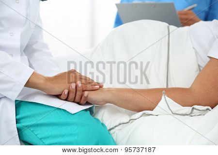 Friendly Female Medicine Doctor's Hands Holding Pregnant Woman's Hand
